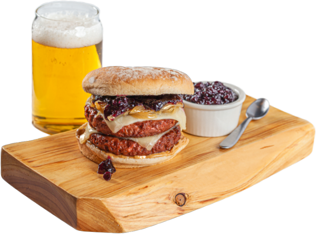 PB&J Burger made with OZO plant-based burger on a wooden block with a beer