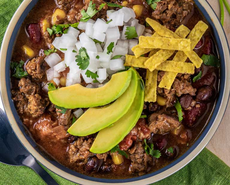 Taco soup made from OZO plant-based ground with onions, avocado and tortilla strips
